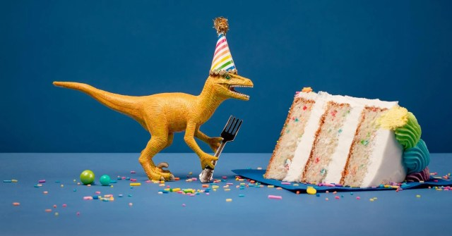 Toy Dinosaur holding a fork next to a slice of birthday cake on a blue background.
