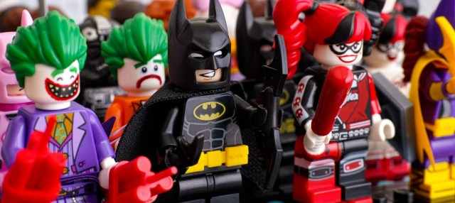 Lego minifigures standing in rows. In first row - Batman, The Jo