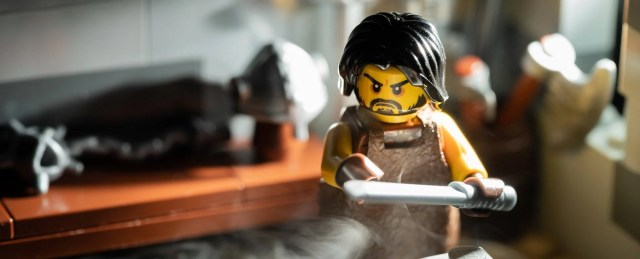 A photo of a LEGO forging his sword.