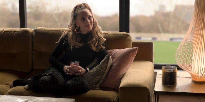 Keeley played by Juno Temple sits on a leather couch with a drink