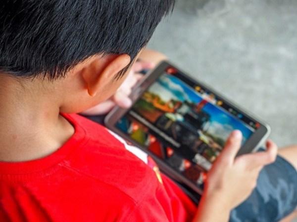 Menino jogando em dispositivo móvel