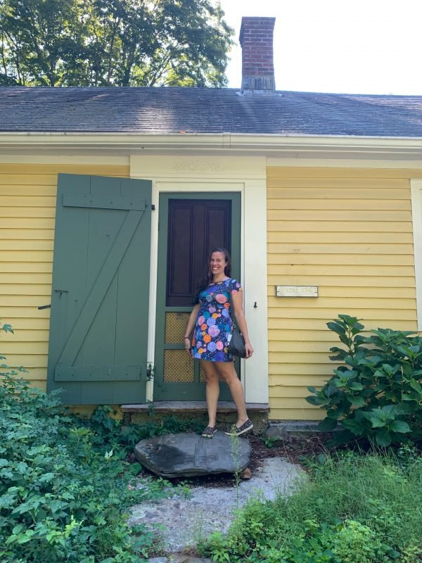 The author standing outside the front door of her yellow house.
