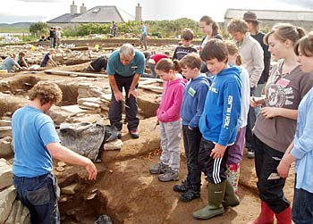 Dan shows the young archaeologists the 'mega pot' Martin has been excavating.
