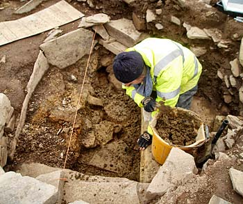 Claire gets to grips with the deposits that underlie the massive paving slab in Structure 10.
