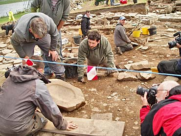 The quern from St 14 is studied while being recorded by National Geographic's photographer Jim Richardson.
