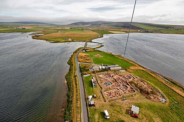 Looking over the excavation site towards the Brig o' Brodgar and the Standing Stones of Stenness.