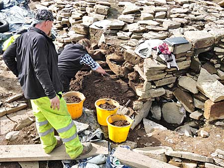 Jan removes the last of the robber material from the east wall of Structure Ten to reveal more of the original building.