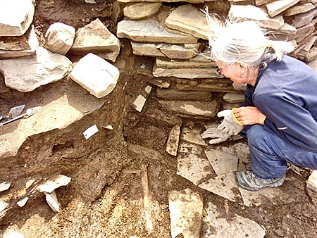 Jenny reveals the new heart h and stone box disappearing under the later north wall of Structure Twelve,