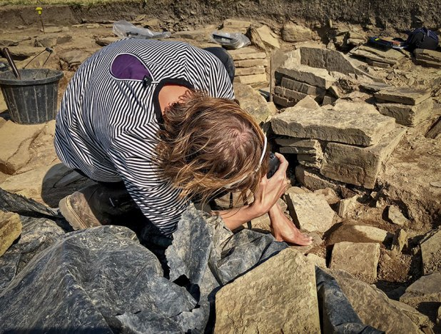Antonia photographs the new incised stone from Structure Five.
