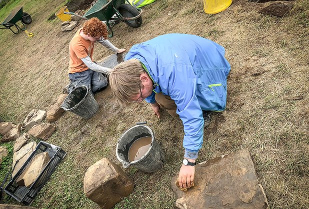 Travis and Emmanuel cleaning stone recovered from the environs of Structure Twenty-Six.