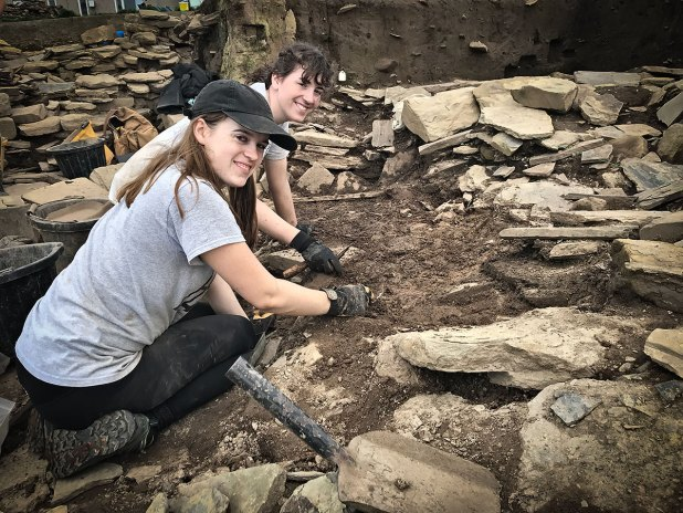 Alison and Kenna excavating beside the outer wall of Structure Thirty-Three.