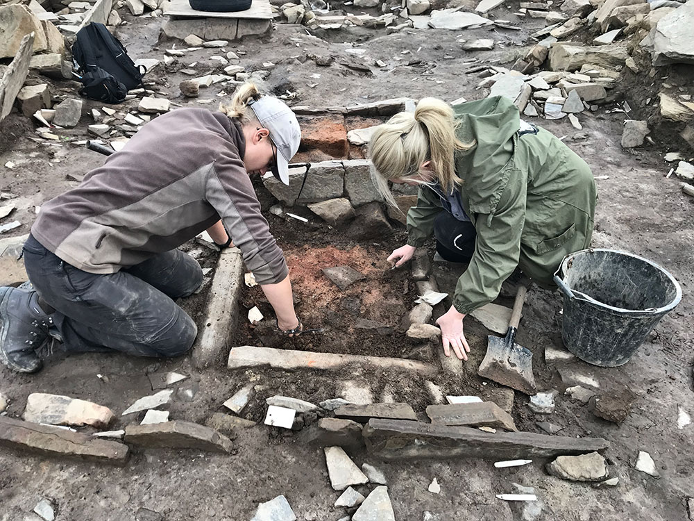 Tonia and Natalie expose the hearth in Structure Seventeen.