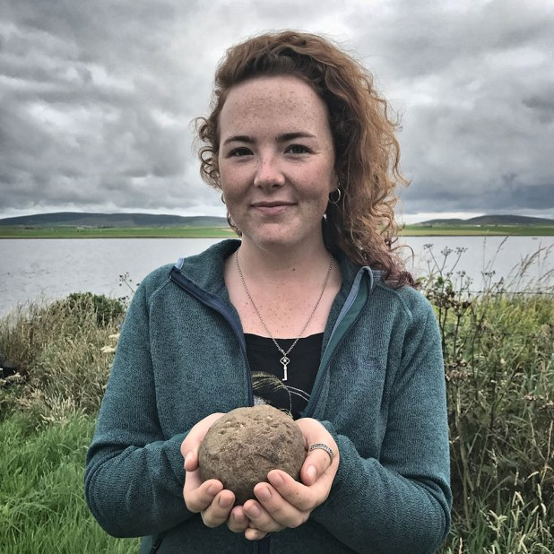 Holly with the hammerstone recovered from Structure Ten.