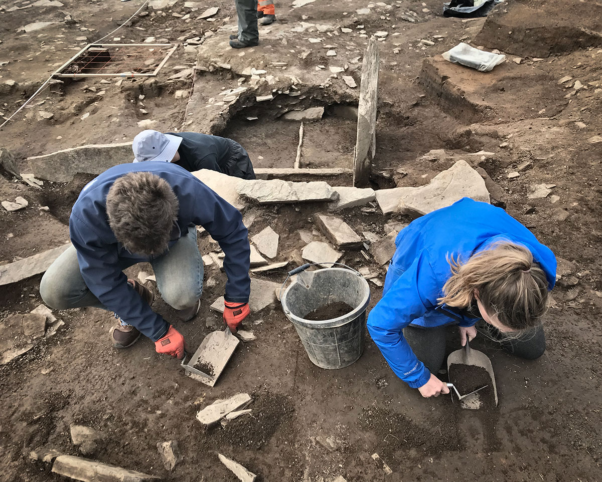 Mary and Brett expose the demolition layer of the eastern wall of Structure Twenty-Seven.