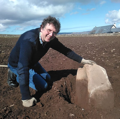 Chris Gee, from the Orkney Research Centre for Archaeology, with the massive saddle quern revealed by ploughing earlier this month. (Ragnhild Ljosland)
