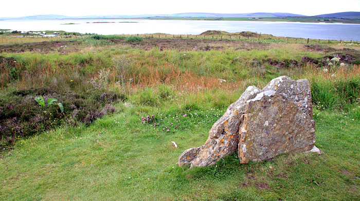 The megalith stump in the Ring of Brodgar featuring the twig-rune inscription. The remains of 'Plumcake Mound' are visible in the background. (Sigurd Towrie)