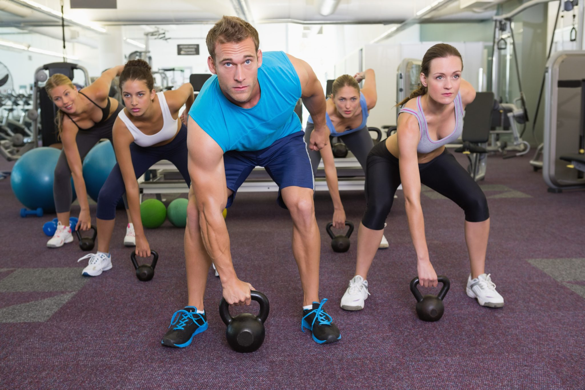 a male trainer with kettlebell certification instructs a kettlebell class