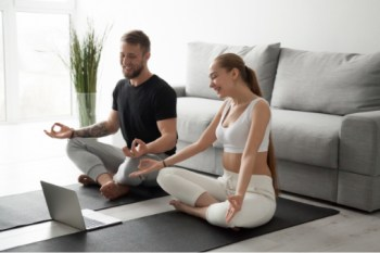 Become a yoga instructor, Man and woman looking at computer while holding a yoga pose