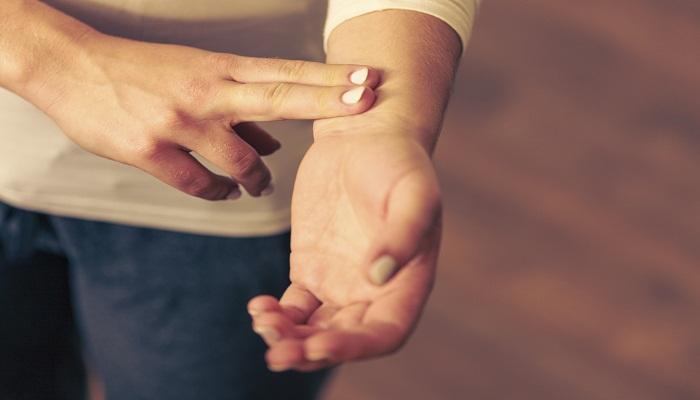Woman checking pulse on wrist closeup