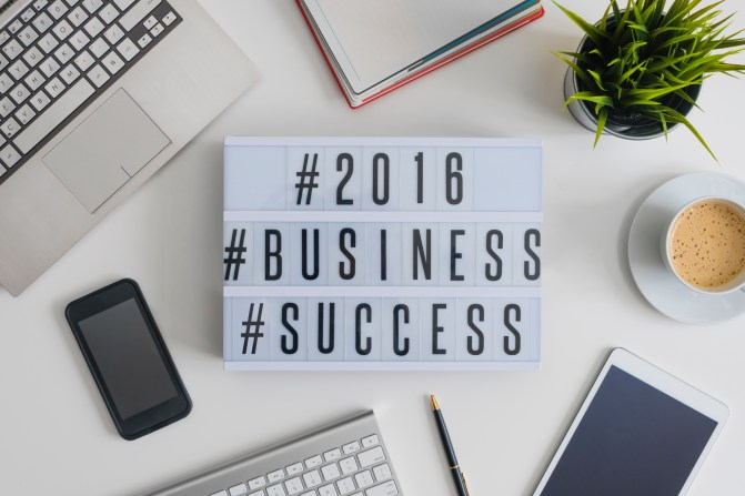 2016 business success hashtags on office table with computer, coffee, notepad, smartphone and digital tablet