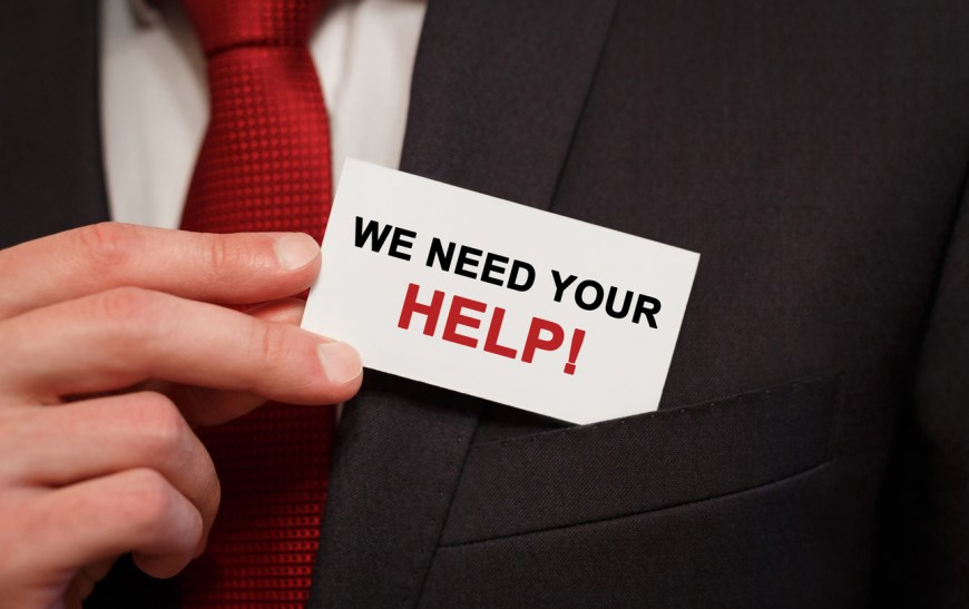 Businessman putting a card with text We need your Help in the pocket