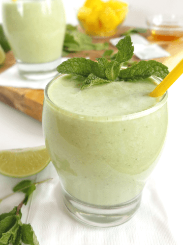 green smoothie with yellow straw and ingredients like pineapple in the background