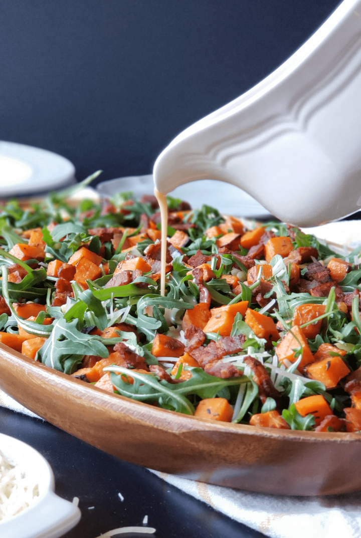 Roasted sweet potatoes and arugula come together with pine nuts and a mouth watering maple bacon vinaigrette to make an incredibly flavorful winter salad! Primal, low carb and easily made Paleo, this Roasted Sweet Potato & Arugula salad will have everyone coming back for more.