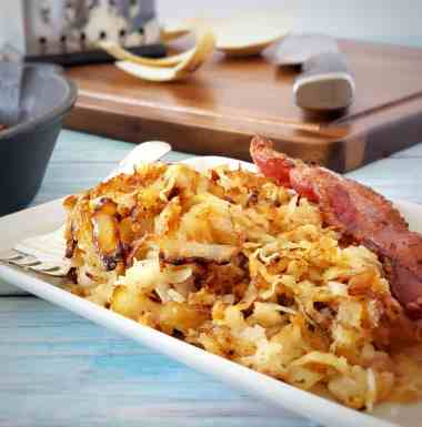 close up of jicama hash browns on a plate with bacon