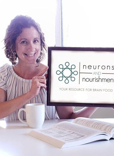 """Laura Duffy, food blogger at Taste Abounds, holding a sign that says """"Neurons and Nourishment"""""""