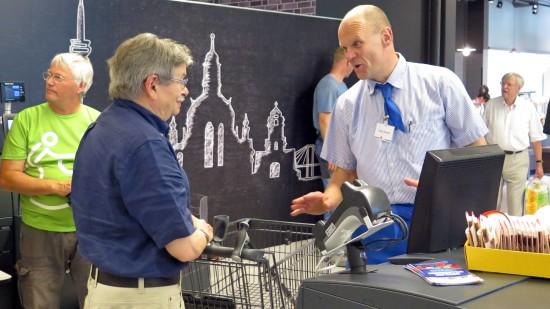 Inhaber Peter Simmel erläutert Kunden das Kassensystem