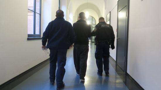 Der Angeklagte (Mitte) wird von zwei Justizbeamten abgeführt.