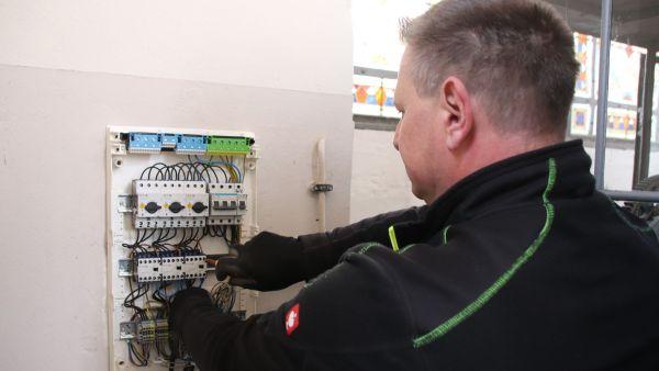 Elektriker Thomas Punsch am Schaltkasten für das Uhrwerk.