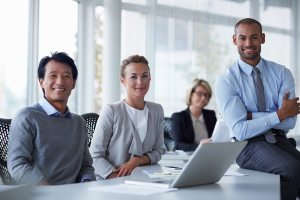 Portrait of confident businesspeople at office desk