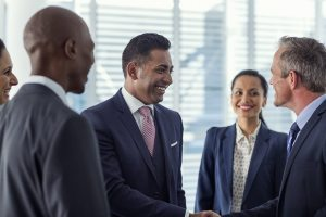 Happy multi-ethnic businesspeople shaking hands in office