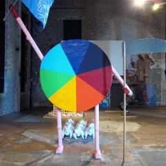 Full Spectrum Dominance Leading the Sheeple // Papier mâché, Acrylic Paint, Wood, Glue, Cardboard, Steel, UN / NATO Flag, PVC Gloves, Inflatable Sheep, Aluminium Tape // 6 x 2 x 5 m // 2013
