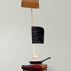 The Jimmy Durham Spilt Milk Fountain (Budget Version) // Box-steel Stool, Frying Pan, Water Pump, Cardboard Box, Wood, Paint, Milk Carton, Text, Digital Print // 210 x 35 x 35 cm // 2004