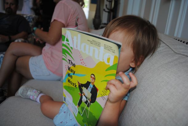 Baby reading Atlanta magazine