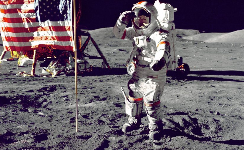 Apollo 11 astronaut in space suit saluting while standing next to American flag and lander on the moon