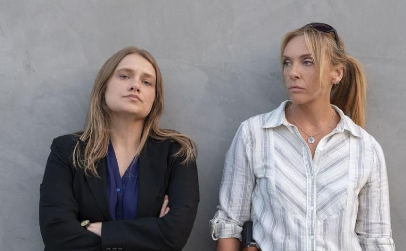 Two main detectives starring in the mini-series Unbelievable standing against a wall
