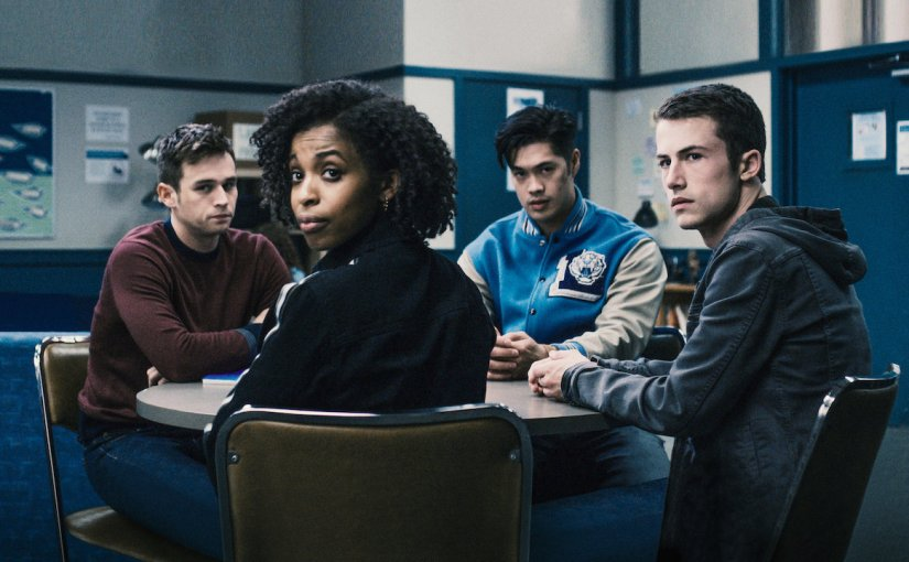 Students starring in the show 13 reasons why season 3 turning to look at the camera while sitting a table in school.