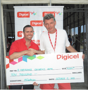 Digicel CEO Johnny Ingle handing over presentational cheque to Sebastian Mottram, Chairperson of the St. Christopher Children's Home