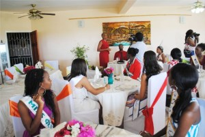 : The Hon Marcella Liburd (standing in the background, left) addresses the contestants and their chaperons