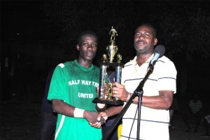Area Parliamentary Representative the Hon Shawn Richards presents the National Caribbean Insurance Ltd Sandy Point Community Football League trophy to Captain Charles Thomas of the Glen 'Ghost' Phillip Half Way Tree United FC.