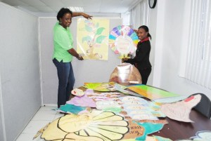 Mrs Agatha Caines, PEP Office Manager (left) and Mrs Diana Pemberton, PEP's Assistant Training Coordinator displaying some of the charts that were made by the Teaching Assistant Officers.
