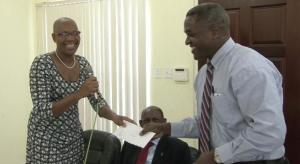 : Min Marcella Liburd hands over cheque to Dr.Wilkinson