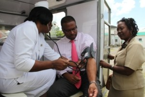 Deputy Premier of Nevis and Minister of Health Hon. Mark Brantley gets his blood pressure checked in a tri-ambulette by Matron at the Alexandra Hospital Aldris Dias while Public Health Nurse Ermine Jeffers looks on moments after the handing over ceremony of three tri-ambulettes from Dubai, United Arab Emirates through the Federal Government concluded at the grounds of the Alexandra Hospital on February 24, 2014