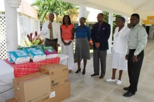 (l-r) Hospital Administrator Gary Pemberton, Vice President of the Nevis Association of South Florida Avonelle Hanley, Supervisor of the Flamboyant Nursing Home Ena Sutton, Acting Premier of Nevis and Minister of Health in the Nevis Island Administration Hon. Mark Brantley, Acting Matron at the Alexandra Hospital Sister Andriene Ward-Stanley and Assistant Hospital Administrator Johnson Morton during a handing over ceremony at the Flamboyant Nursing Home on May 19, 2014