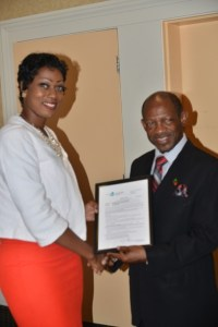 St. Kitts and Nevis' Prime Minister the Right Hon. Dr. Denzil L. Douglas (right)  presents certificate to Ms. Monique Lescott of St. Kitts to study medicine.