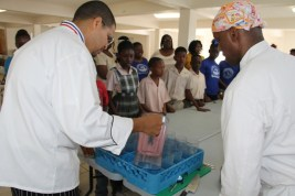 (L-R) Food and Nutrition Specialist attached to the School Meals Programme on Nevis, Executive Chef Michael Henville and Celebrity Chief of Atlanta Marvin Woods,   demonstrates to students of the Charlestown Primary School how to make healthy snacks at a Mini Chief Academy session at the school's kitchen on February 24, 2015