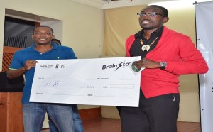 Rodney Browne (left) of Arts Arise handing over cheque to James Galloway the winner of the Brainstorm Spoken Word Slam